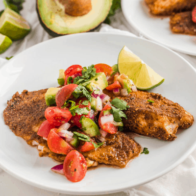 Whole30 Blackened Cajun Tilapia served with Avocado and Tomato Salsa on a white plate.