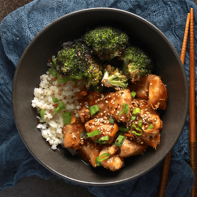 Whole30 Chinese Orange Chicken served in a black bowl with cauliflower rice and broccoli.