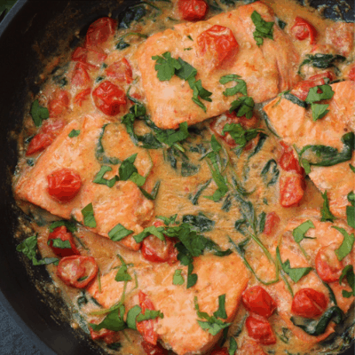 Whole30 Creamy Skillet Salmon cooking in a skillet.