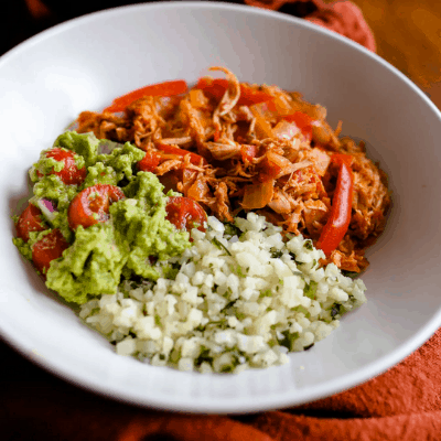 whole30 chicken taco meat served over cauliflower rice with peppers, onions, and guacamole in a white bowl
